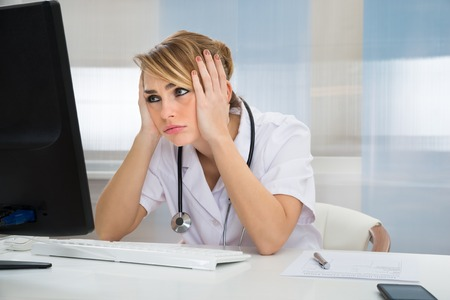39944318 - young female worried doctor looking at computer in clinic
