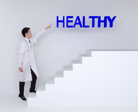 53974594 - male doctor stepping up on stairs and pointing to healthy